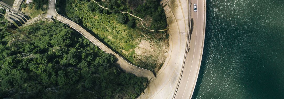 Aerial view of moving car on road over dam, river