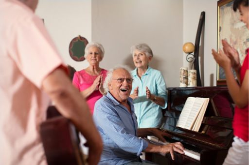 Elderly aged care residents sit around a piano laughing and enjoying music