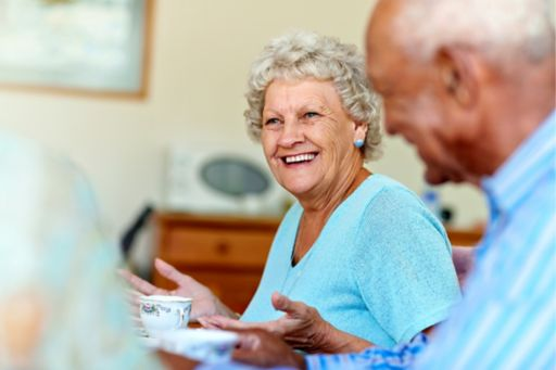 Senior woman spending leisure time with friends in aged care setting