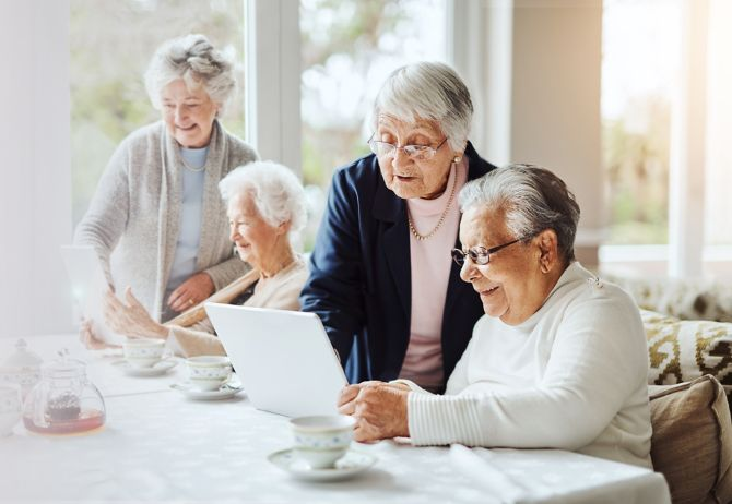 Group of senior women using a digital tablet together at a retirement home