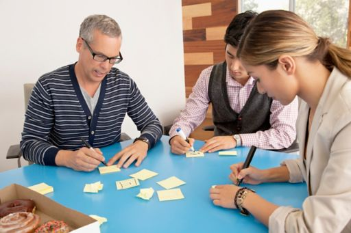 Office people writing on sticky notes