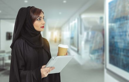 Arabic woman holding tablet and coffee