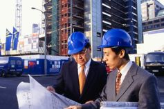 KPMG Impacts on the construction industry of the new revenue standard (IFRS 15) publication image: two architects discussing blueprints at a construction site