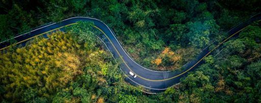 Arial view of highway curve road in forest