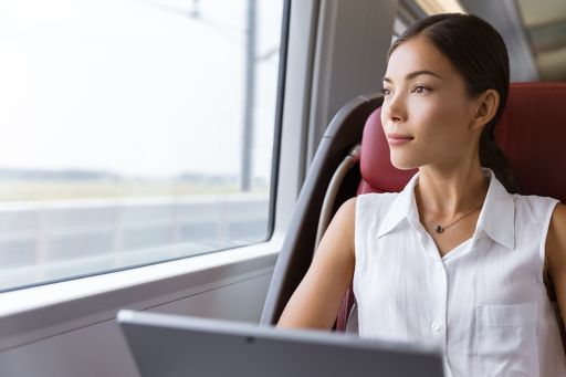 A woman works on a laptop while travelling by train