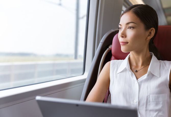 Businesswoman pensive looking out the window while working on computer on travel commute to work.