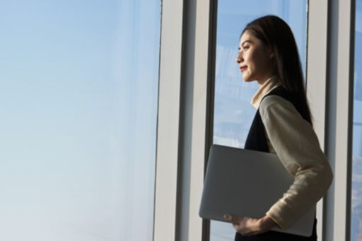 Woman looking out window into sky