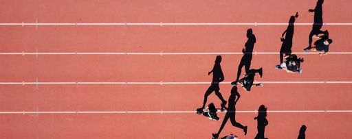 Top view of athletes running on track with shadows