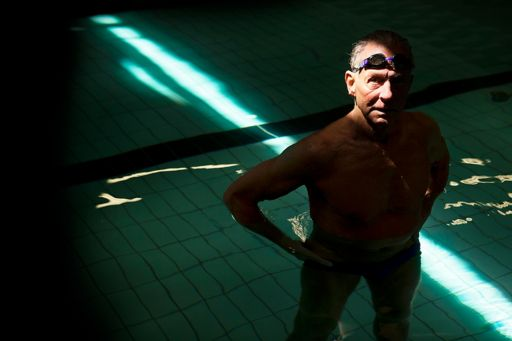 Baby boomer standing in shadowy swimming pool