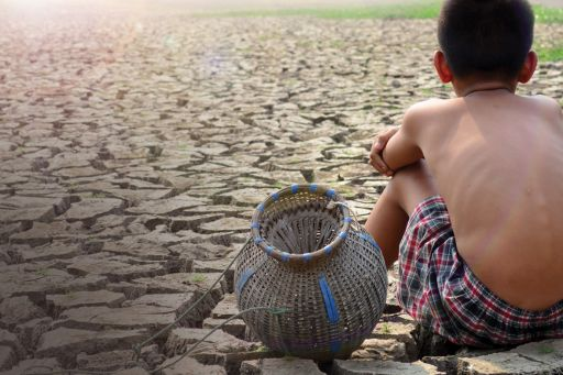 Back-view of boy with empty pot sitting on a barren land looking sunrise