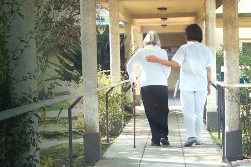 Back view of female doctor helping elderly woman with walker in the hospital garden