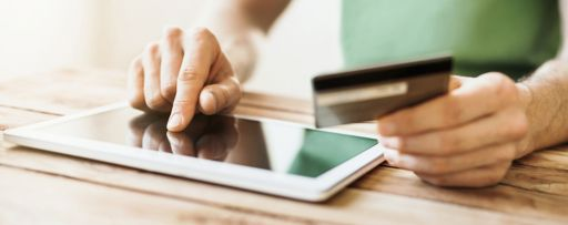 Man using tablet with credit card in other hand