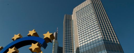 Big blue euro sign with golden stars in front of tall building