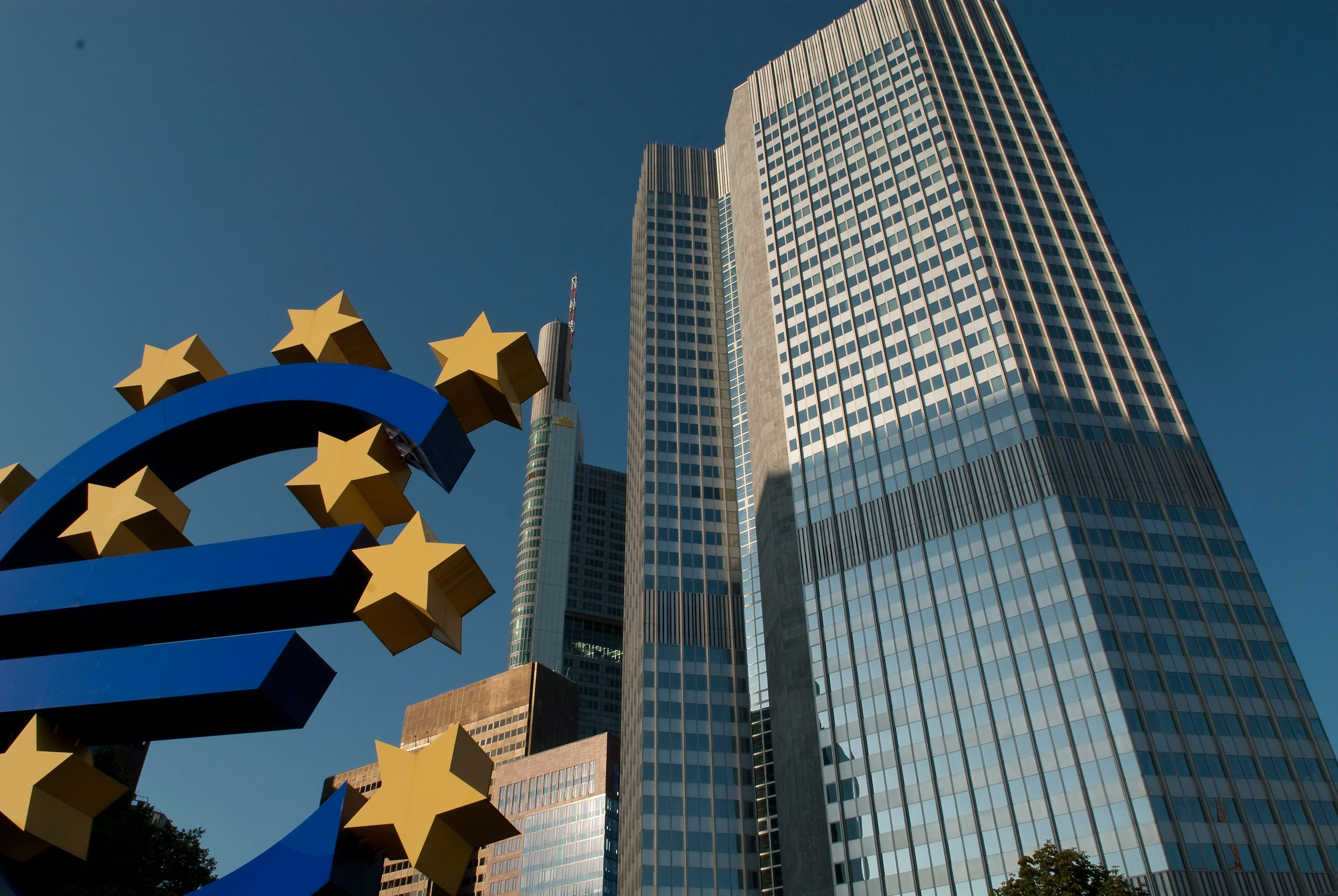 Big blue euro sign in front of tall building