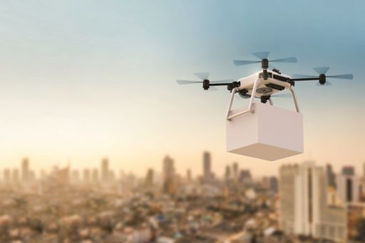 Black and white drone flying against city sky background