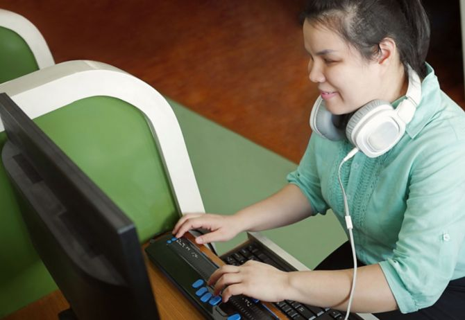 Blind person wearing headphones using computer with braille