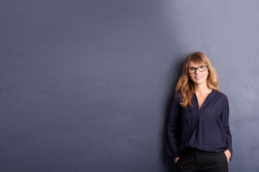 Blonde business woman standing against a grey wall