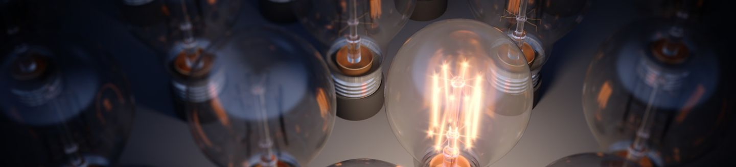 Glowing Light Bulb between the others. Can be used leadership, innovation and individuality concepts.