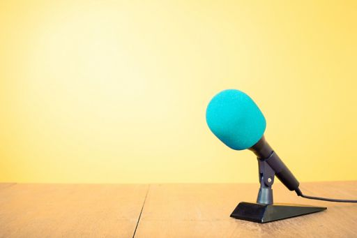 Blue microphone in front of yellow wall