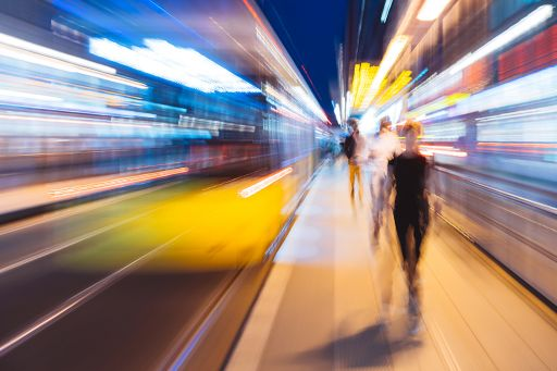Blurred image of three people walking at a metro station