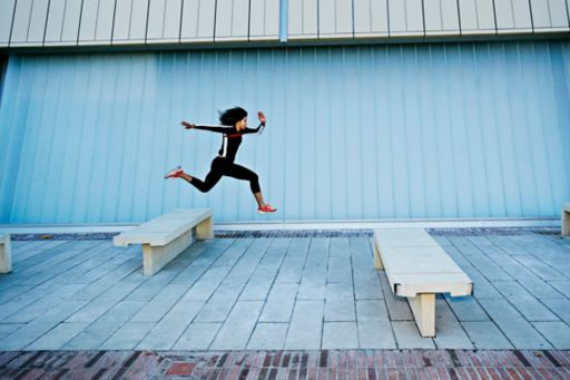 Woman jumping from bench to bench