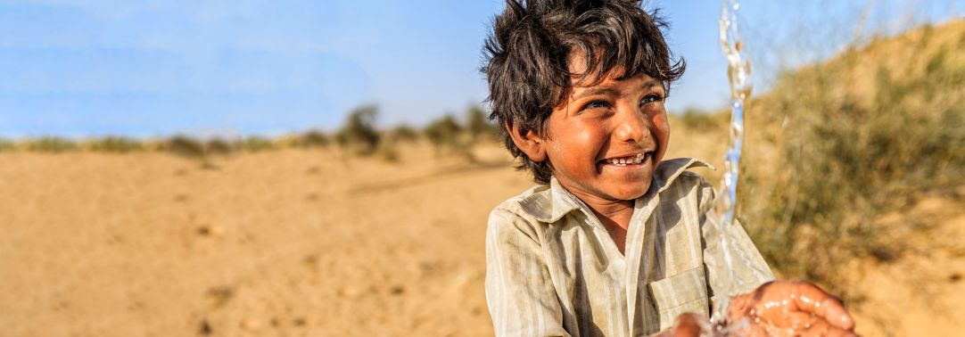 Boy child smiling at touching water sand in the background