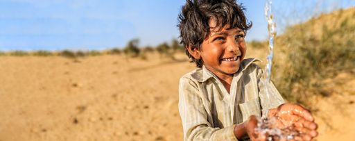 Boy child smiling as water is poured into his hands