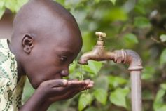 Boy drinking water through tap