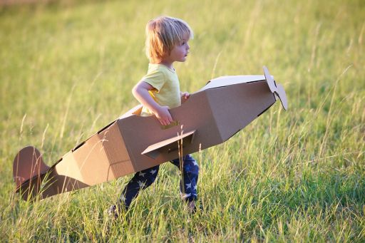Boy flying airplane outdoors