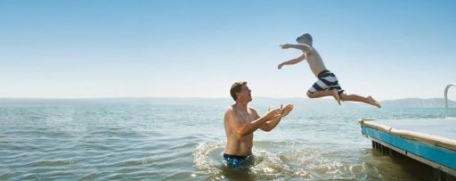 Boy jumping into a lake into his father's arms