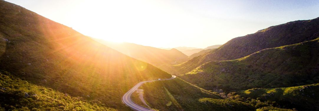 Sun shining above green mountains around a spiral road, scenery