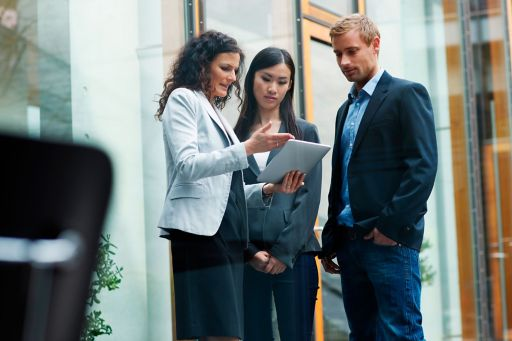 Woman holding a tablet computer and having a conversation with two other people