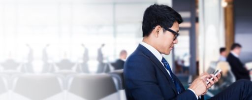 business man sitting airport looking at smartphone