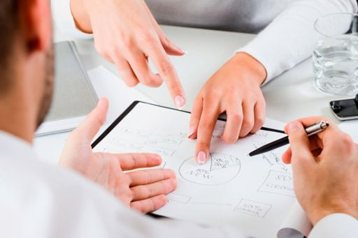 Two people discussing graphs in a meeting