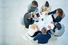 Group of business people meeting around a white table