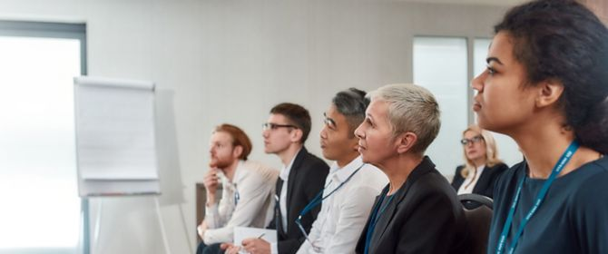 Business people sitting in front row attending a conference