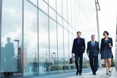 business-people-walking-by-glass-building