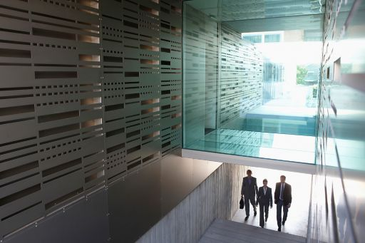 Business people walking up stairs in office