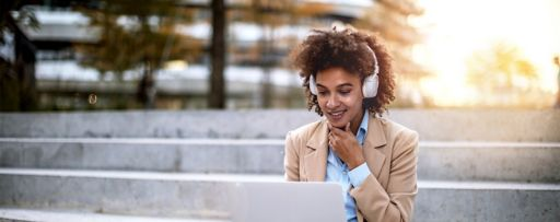 Business woman on a lunch break outdoors using laptop with headphones