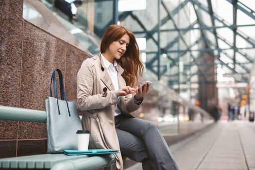 Business woman using smart phone on the city street