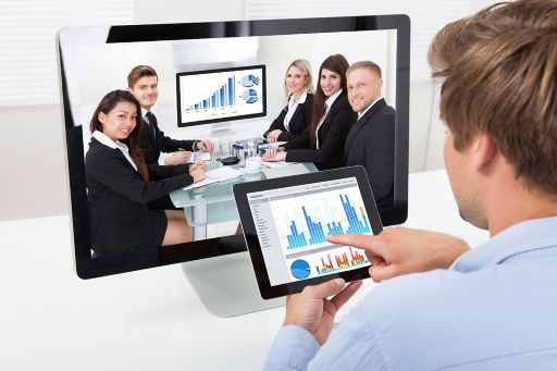 Businessman analyzing graphs on computer while video conferencing