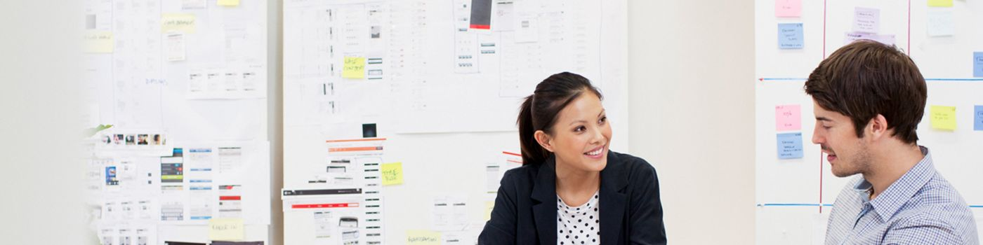 A businesswoman and her colleague in a meeting room with a Kanban board behind them
