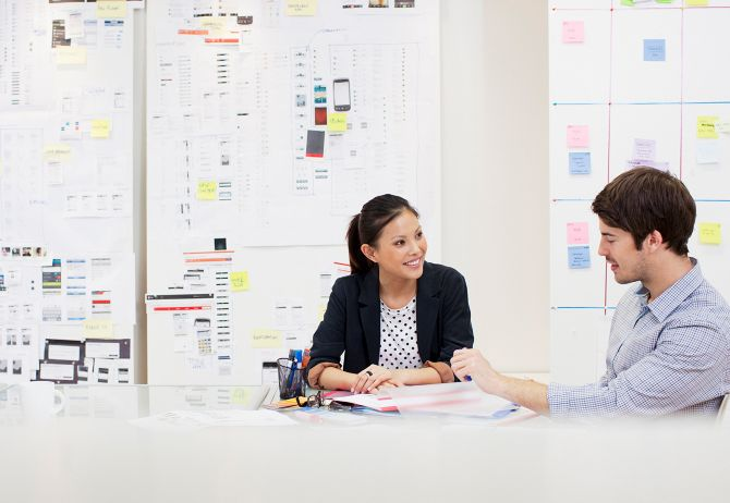 A man and woman in a business meeting with kanban boards behind them