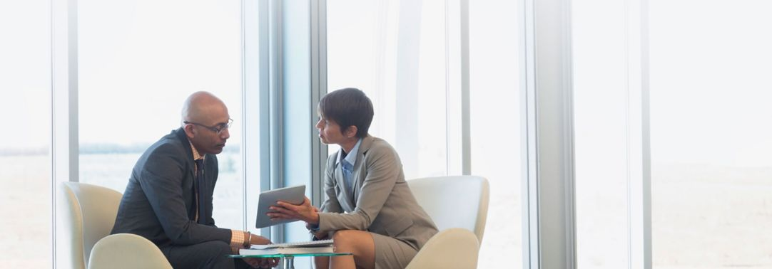 Businessman and woman discussing using ipad