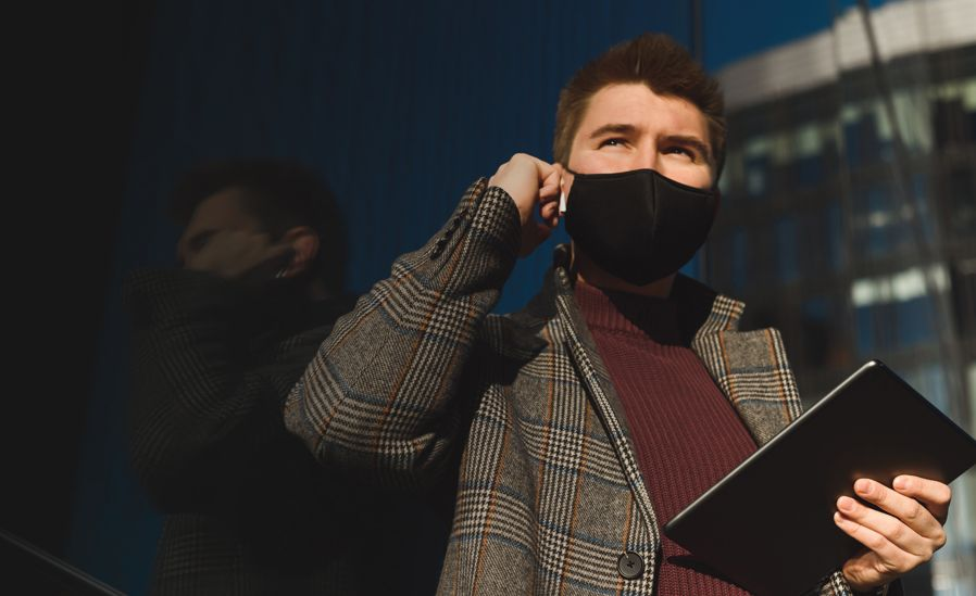 Businessman wearing a face mask taking call via AirPods while holding a touch-screen device