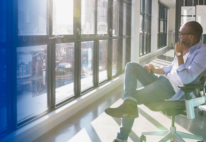 Businessman looking out of office window in deep thought