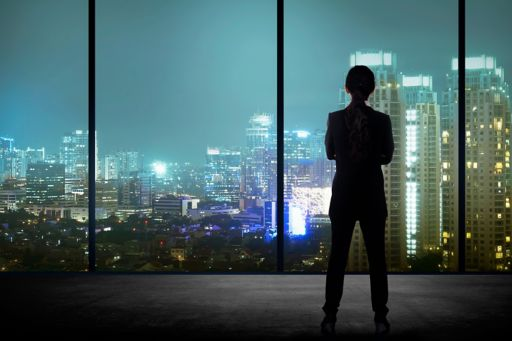Business man looking out window at city lights