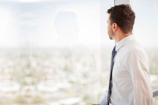 Businessman looking out of glass window