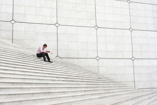 Businessman sitting on staircase reading newspaper