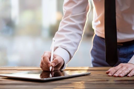 Businessman signing tablet with stylus